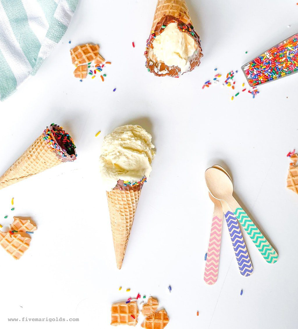 Marshmallow vanilla ice cream cones on white background with sprinkles and spoons